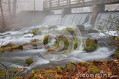 Waterfall under a bridge on a foggy fall morning.