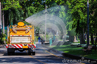 Watering in Public Park with Big Tank Sprayer showing Water mist Editorial Photo
