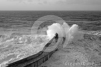 Wave breaks on Portreath pier, Cornwall UK.