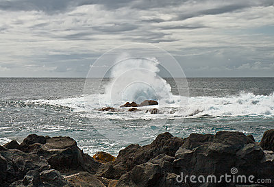 The wave breaks about stones