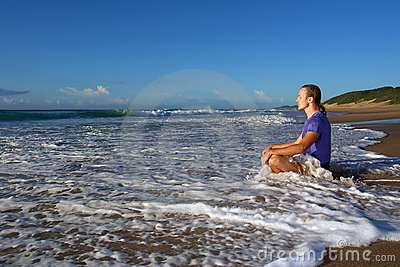 Wave splashes on meditating young man