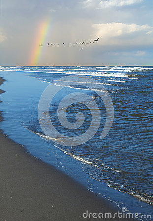 Waves Breaking on Shore with a Partial Rainbow