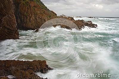 Waves crashing into cliffs