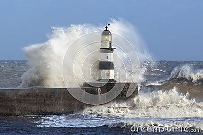Waves crashing over Lighthouse - England