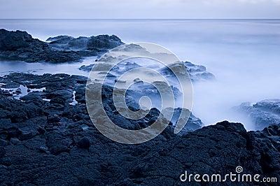 Waves crashing on rocky coast at dusk