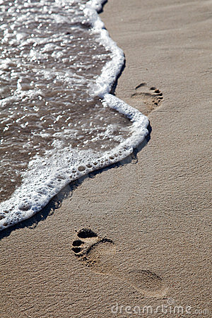 Waves and footprints on beach