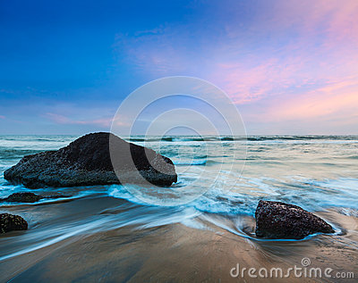 Waves and rocks on beach on sunset