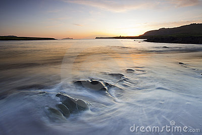 Waves rolling on beach at twilight