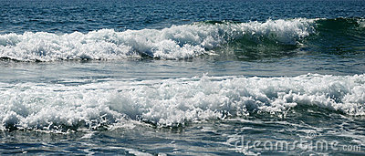 Waves with shining foam against blue sea