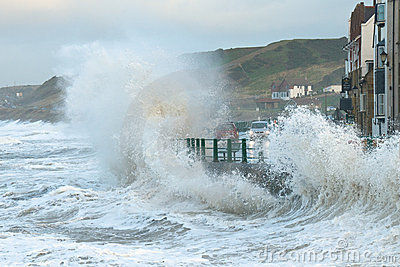 Waves splashing over coast road