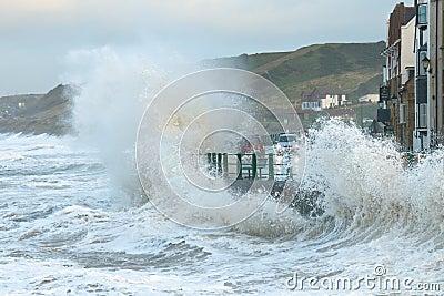 Waves splashing over coast road