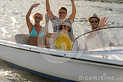 Waving young people sitting in motorboat