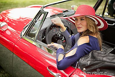 Wealthy lady looking out her classic red european sports car