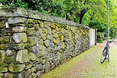 Weathered Stone Wall and Brick Sidewalk