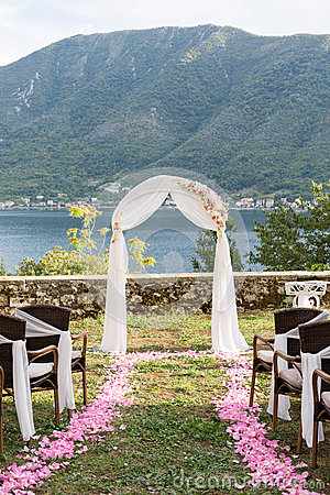 Wedding arch decorated with flowers outdoors Stock Photo