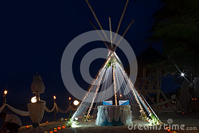 Wedding arch and set up with flowers on beach at night