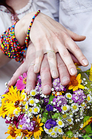 Wedding bouquet from  flowers and hands with rings