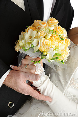 Wedding bouquet in hands of bride and groom, on wh