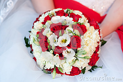 Wedding bouquet in hands of the bride. White and red roses
