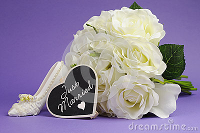 Wedding bouquet with Just Married heart sign against purple background.