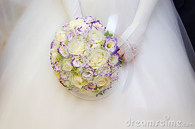 Wedding bouquet with many white roses in hands