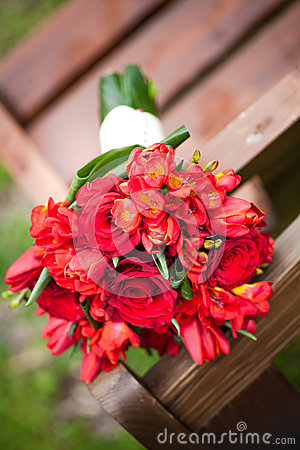 Wedding bouquet of mixed red roses on a bench