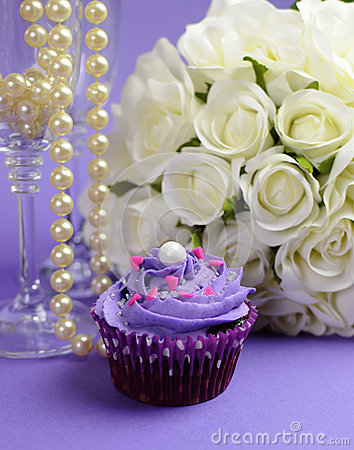 Wedding bouquet with purple cupcake closeup.