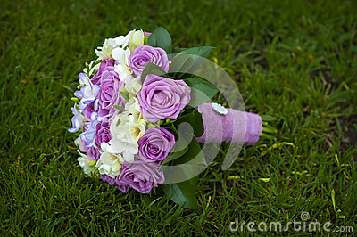 Wedding bouquet of purple and white roses lying on grass