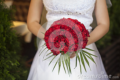 Wedding bouquet of red roses and leaves in brides hands