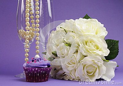 Wedding bouquet of white roses with purple cupcake and pearls in champagne glass