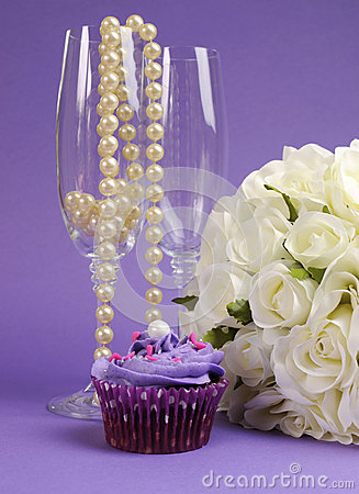 Wedding bouquet of white roses with purple cupcake and pearls in champagne glass - vertical.