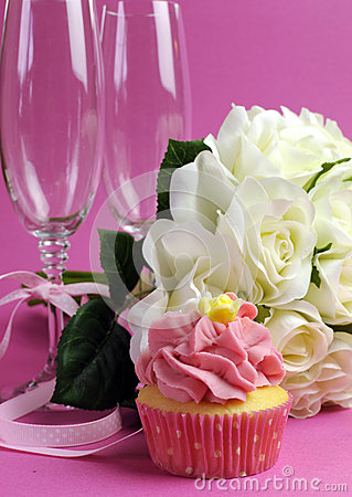 Wedding bridal bouquet of white roses on pink background with cupcake