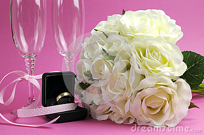Wedding bridal bouquet of white roses on pink background with pair of champagne flute glasses.