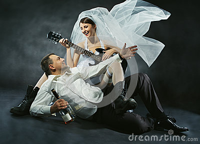 Wedding couple celebrating, singing, drinking and playing guitar