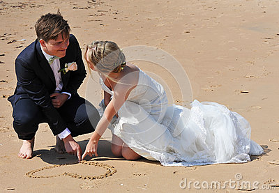 Wedding Couple drawing a Heart in the Sand.