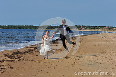 Wedding Couple jumping on the Beach.
