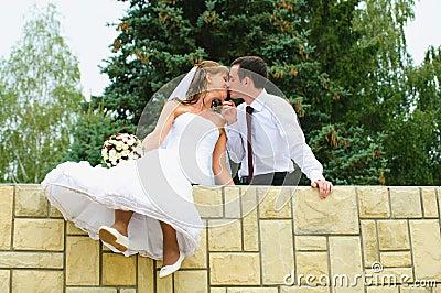 Wedding couple kiss and dangle feet. Tenderness loving