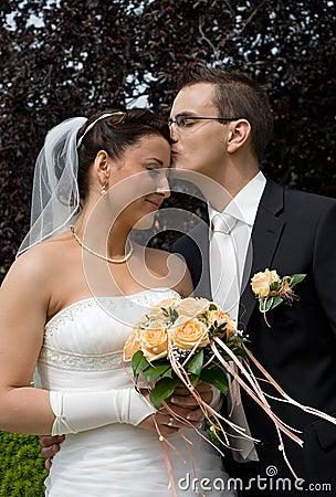 Wedding couple, man kiss brides head