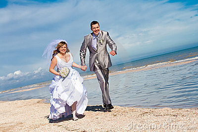 Wedding couple runs on the beach
