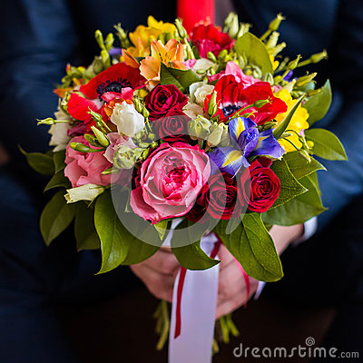 Free Wedding Flowers, Groom Holds Bouquet Of White, Blue, Yellow Flowers And Red Roses Stock Images - 76262014
