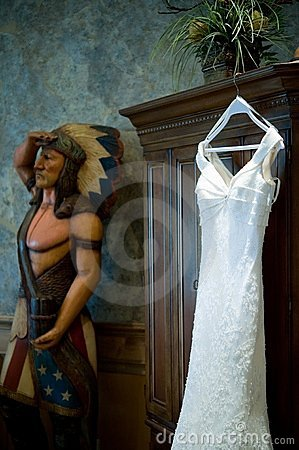 Wedding gown hanging near a cigar indian