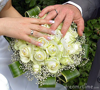Wedding hands and rings on flowers