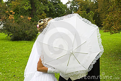 Wedding kiss behind umbrella