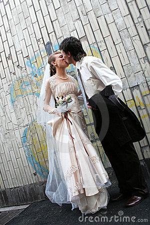 Wedding kiss near the graffity wall