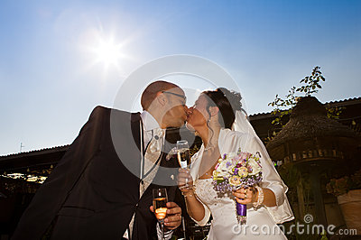 Wedding kiss with sparkling glass