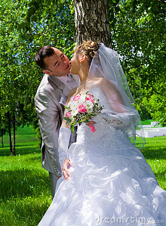 The wedding pair kisses near a tree trunk