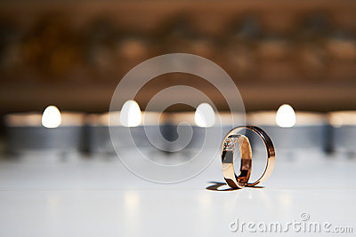 Wedding rings on a background of burning candles