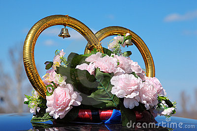 Wedding rings with bouquet on car roof