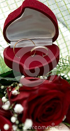 Wedding rings on bouquet of red roses