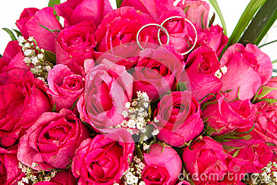 Wedding rings and bridal bouquet isolated over whi